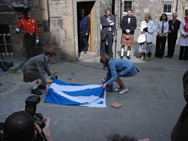Hal and Bella lifting the Saltire from the stone